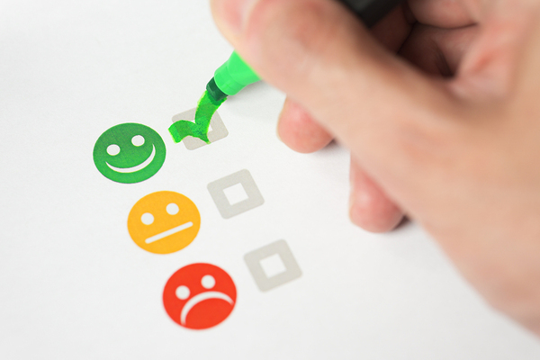 Person checking a smiley face on a review document.