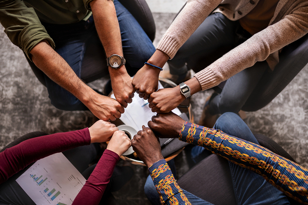 Group of people touching fists together in a circle.