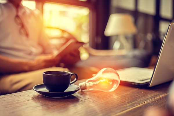 Cup of coffee and lightbulb on a table.