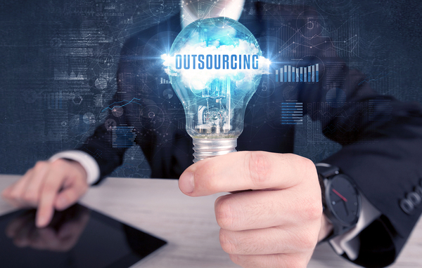Person holding a lightbulb labeled outsourcing.