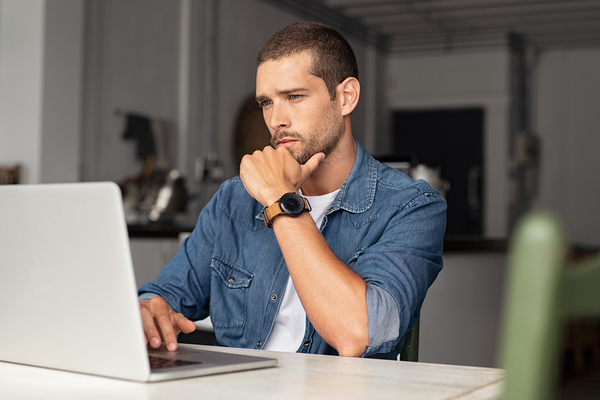 Man looking intently at his laptop computer screen.
