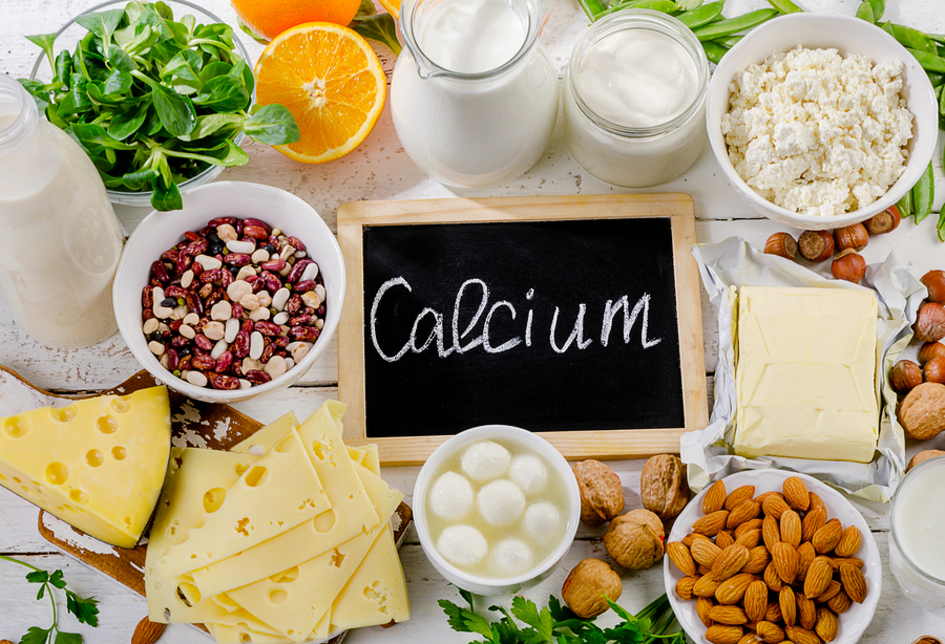 Chalk board with the word calcium surrounded by nuts, cheese and legumes.
