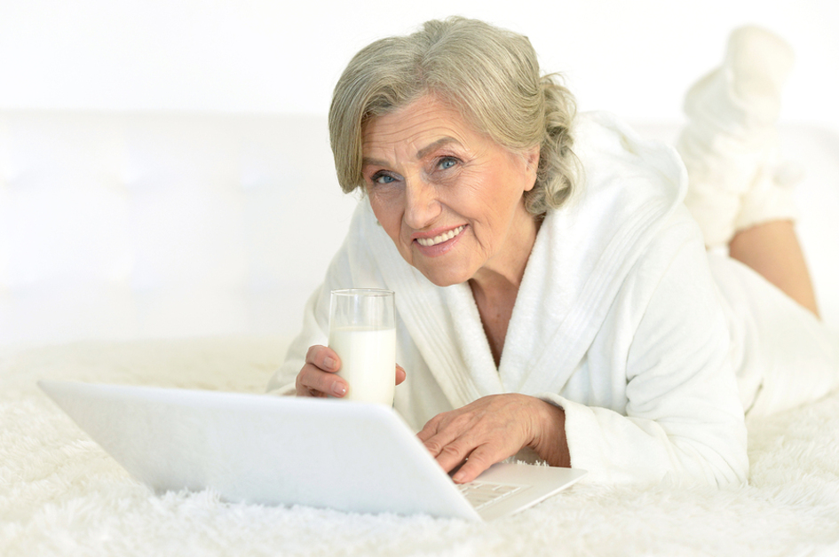 Woman lying down drinking a glass of milk.