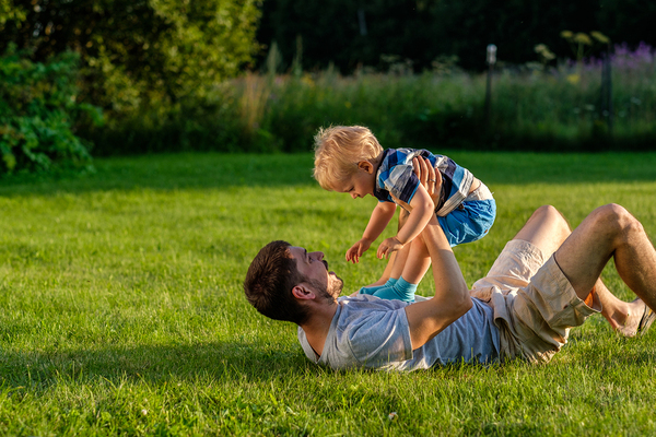 Father lying on the grass lifting his son up and both laughing.