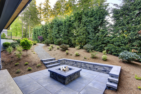 Beautiful patio with stone wall and fire pit in the center.