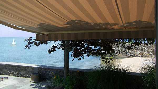 Outdoor awning providing a shaded place and view of the ocean.