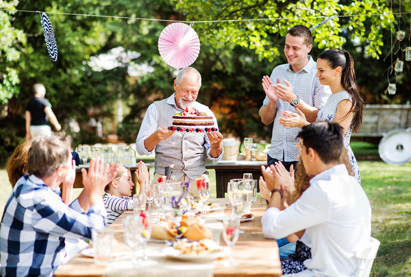 Family sitting around a table outside clapping and smiling.