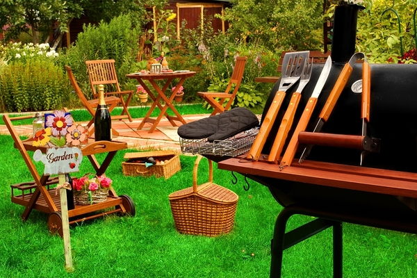 Outdoor barbecue with grille, and wooden seating.