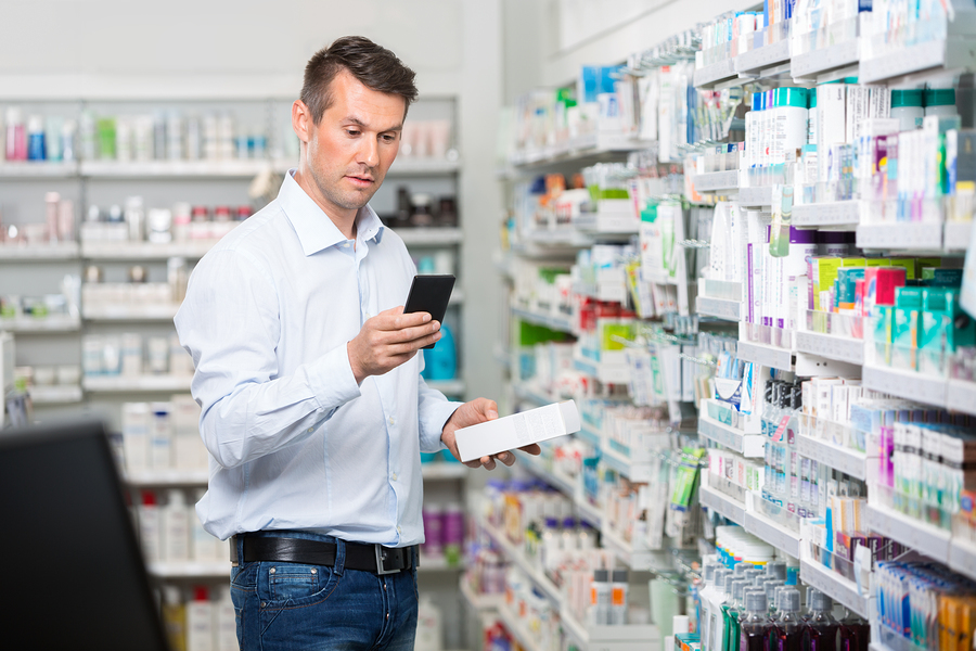 Man shopping for medication while referring to his phone.