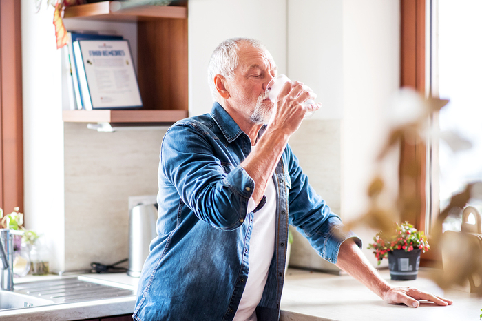 Older man drinking a glass of water.