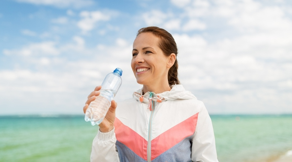 Woman drinking water from a bottle.