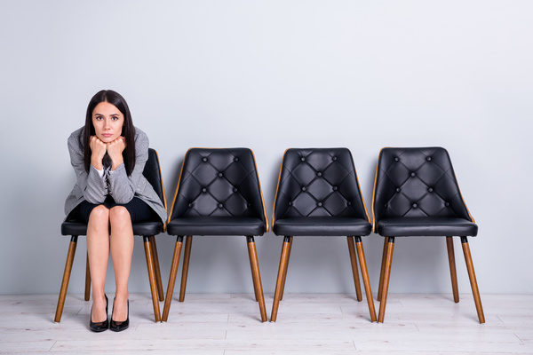 Woman sitting next to three empty chairs.