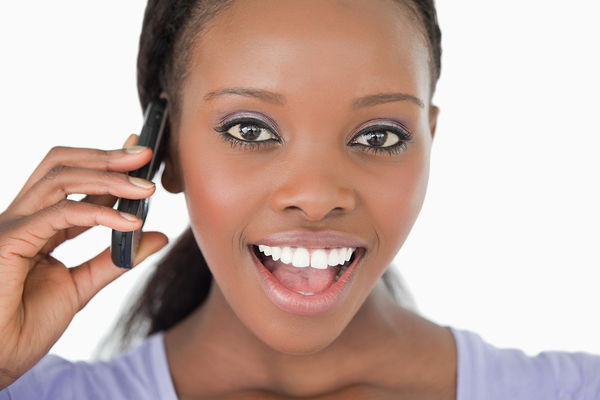 Woman taking on the phone smiling.
