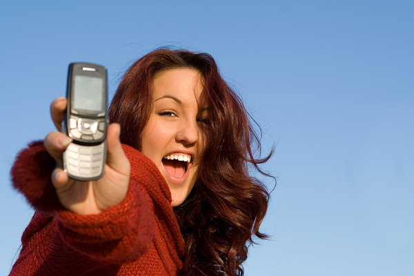 Woman holding out a phone smiling.