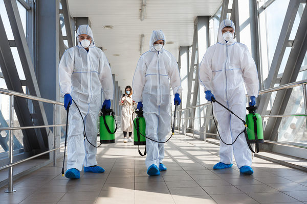 Group of cleaners wearing protective gear.