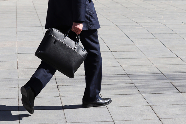 Man walking with a black leather briefcase.