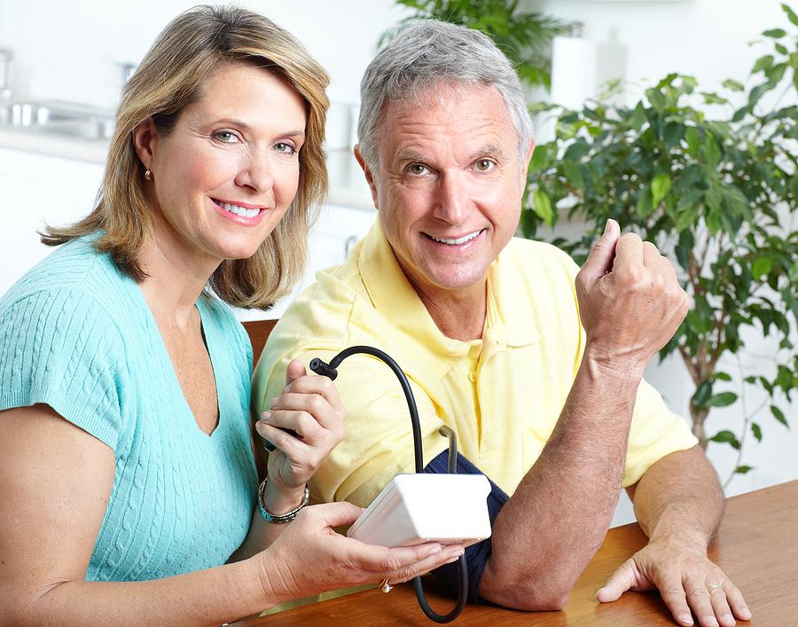 Woman taking a mans blood pressure.