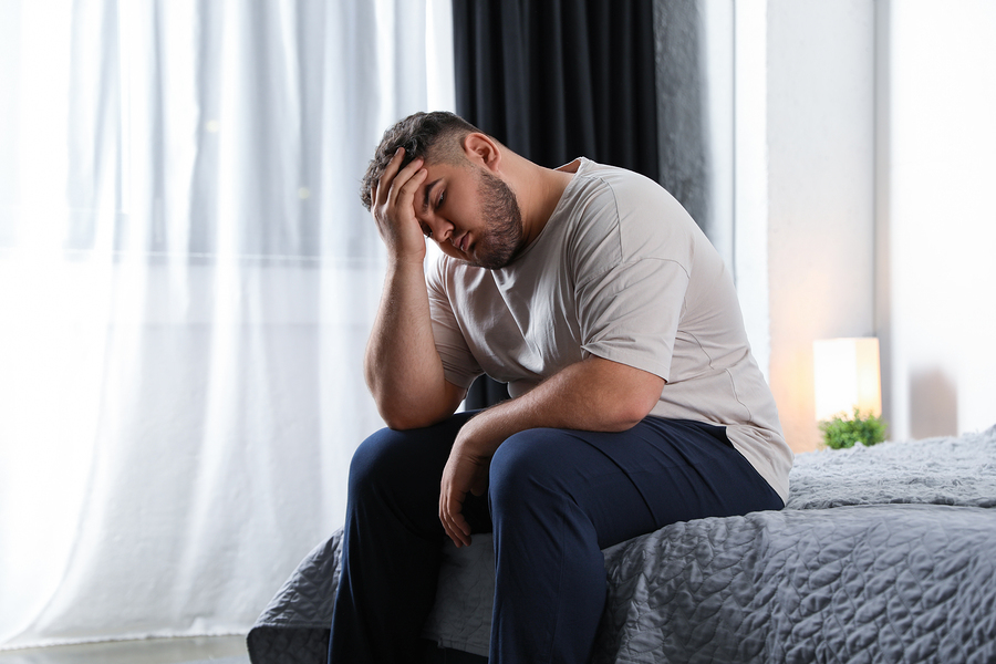 Man sitting at the edge of his bed appearing depressed.