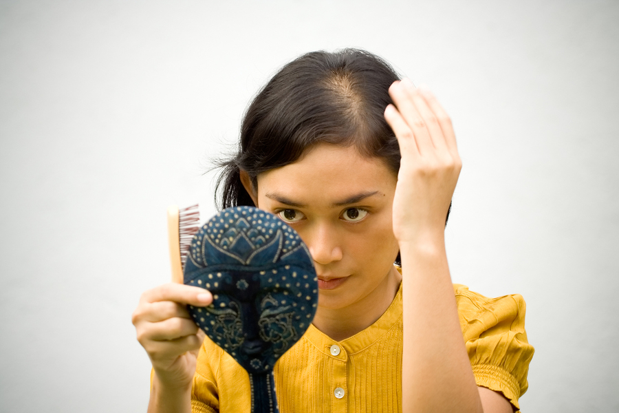 Woman looking at her thinning hair.