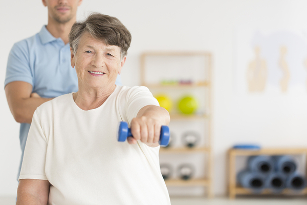 Older woman lifting weights with a physical therapist assisting.