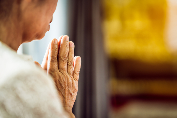 Woman holding her hands in prayer.