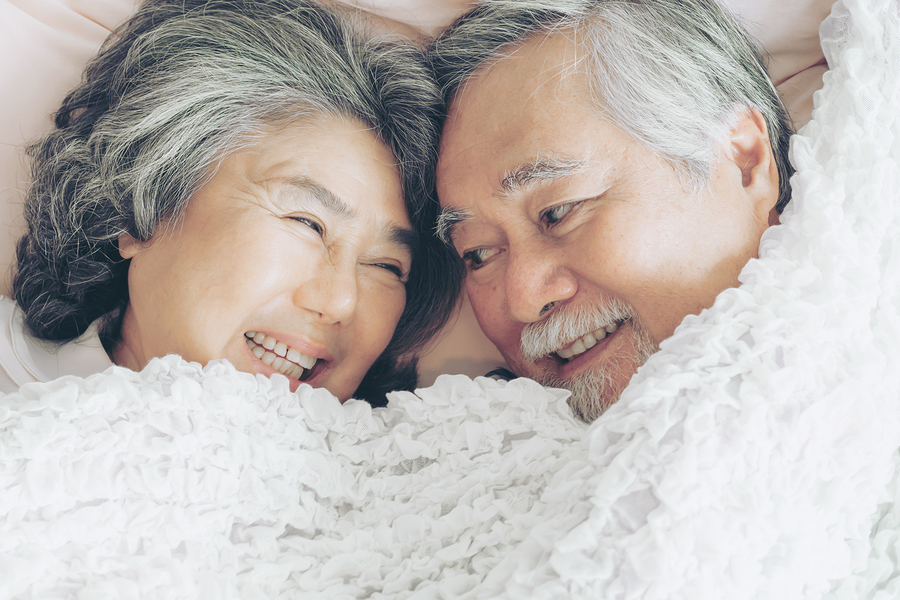 Couple smiling at each other in bed.
