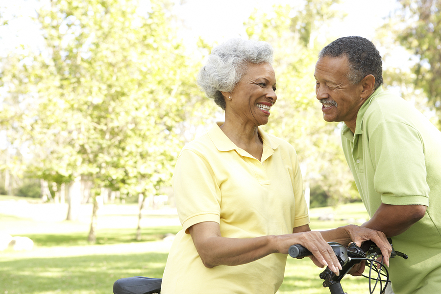 Couple smiling at each other while holding onto bicycles.