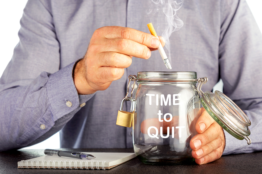 Man putting a cigarette into a jar labeled time to quit.