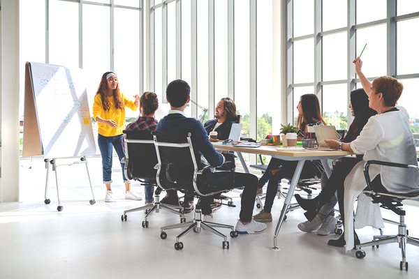 Woman presenting to a a group sitting around a conference table.
