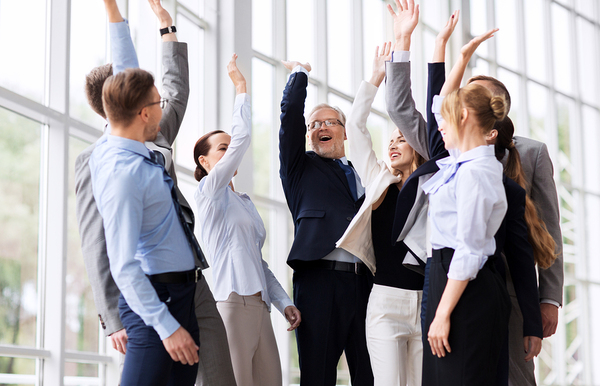 Group of colleagues raising up their arms in triumph.