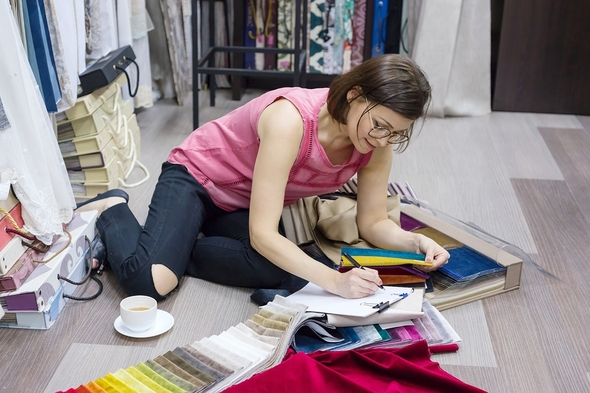 Woman choosing colors for textile items.