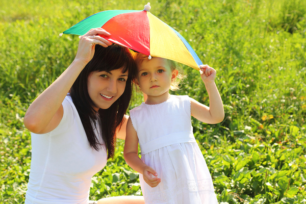Woman and child sharing a small kid-sized umbrella.