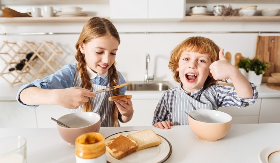 Two kids eating breakfast giving thumbs up.