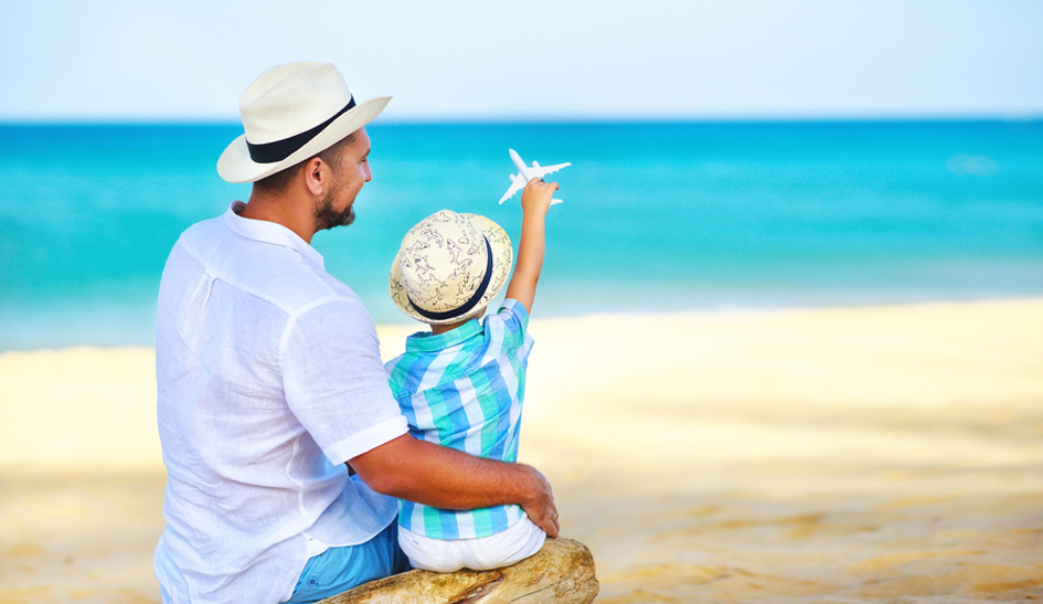 Father and son sitting on a beach.