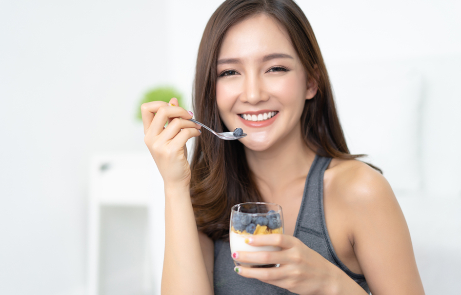Woman eating a cup of fruit.