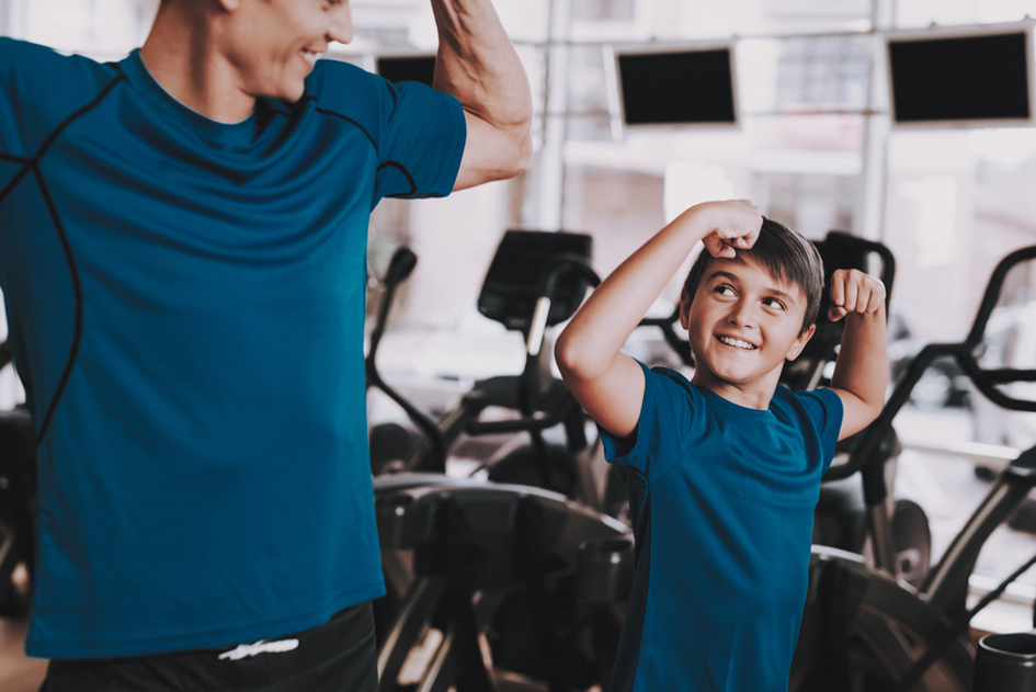 Father and son working out at a gym.