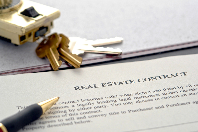 Real estate contract document with keys and a pen.