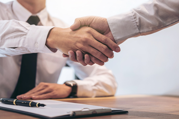 two men shaking hands at a desk