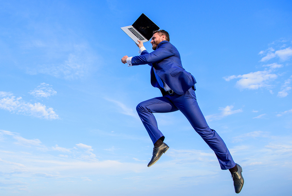 Man jumping in the air with a laptop.