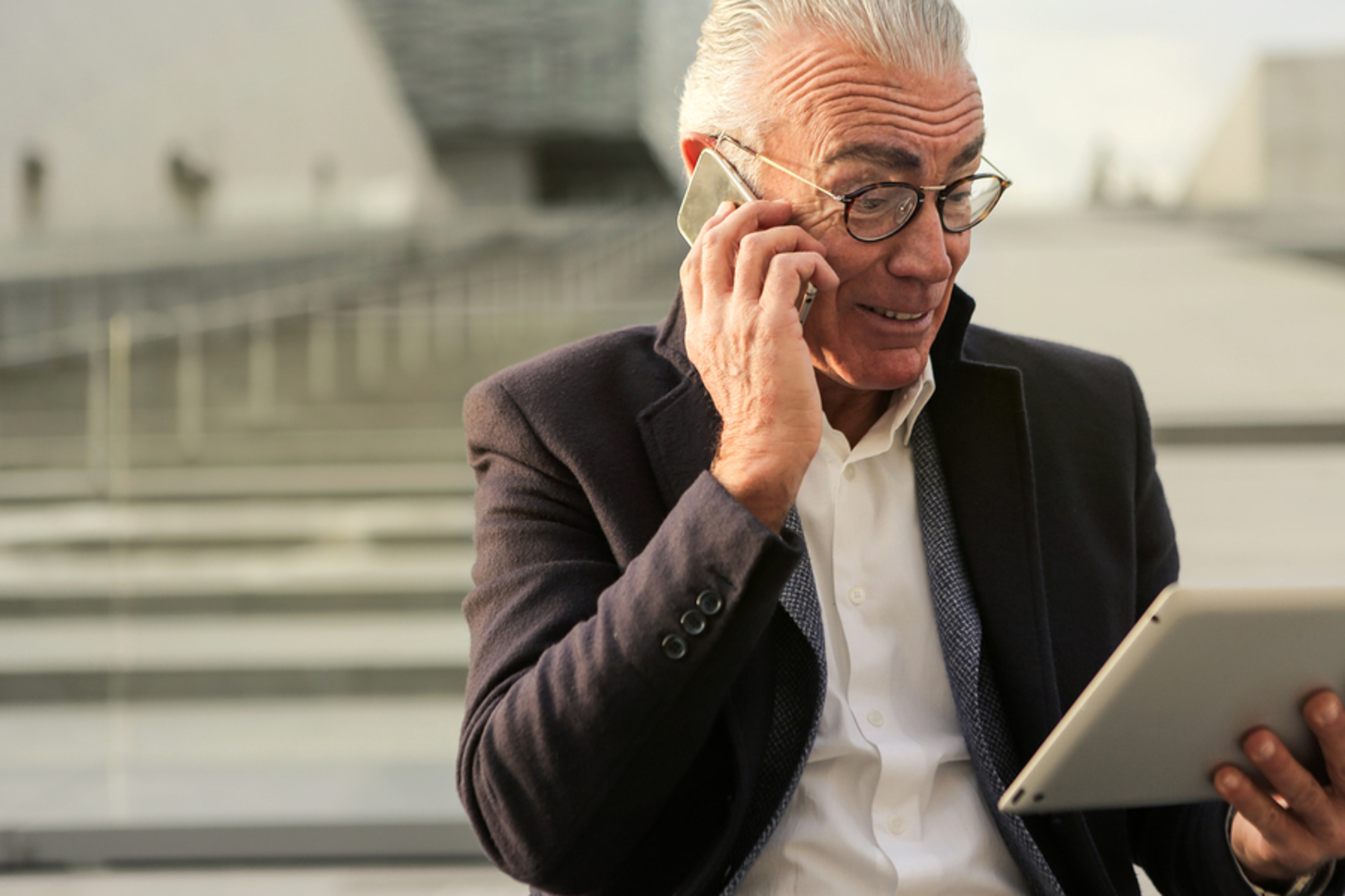 Man looking at a tablet while talking on the phone.