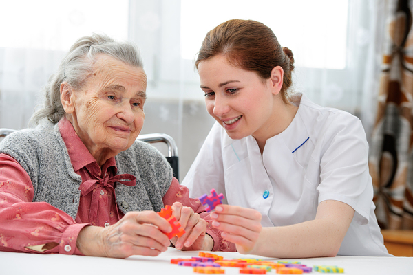 Physical therapy working with an elderly woman at a table with foam puzzle pieces.