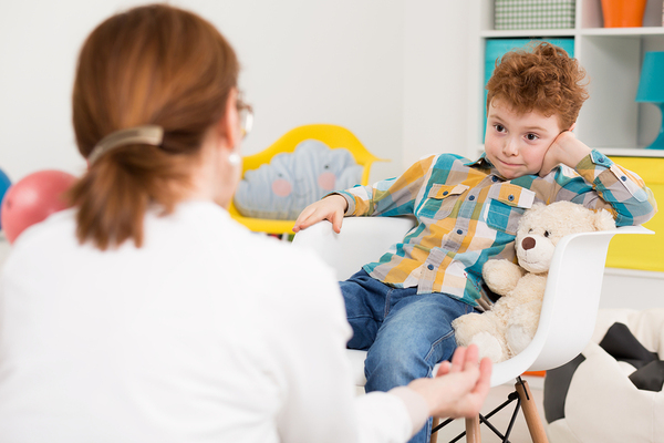 Young boy with a teddybear talking with a therapist.
