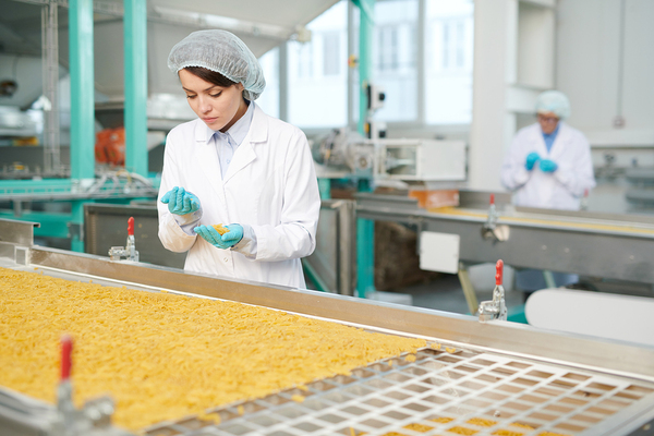 Woman working in a factory inspecting product.