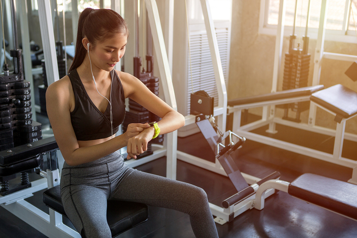 Woman sitting on exercise equipment looking at her watch.
