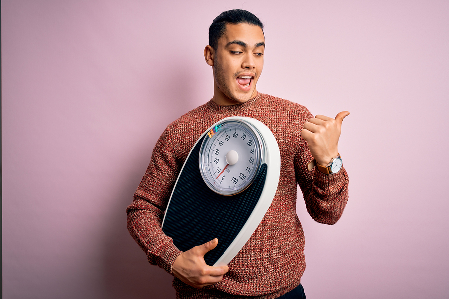 Man holding a scale and thumbs up.