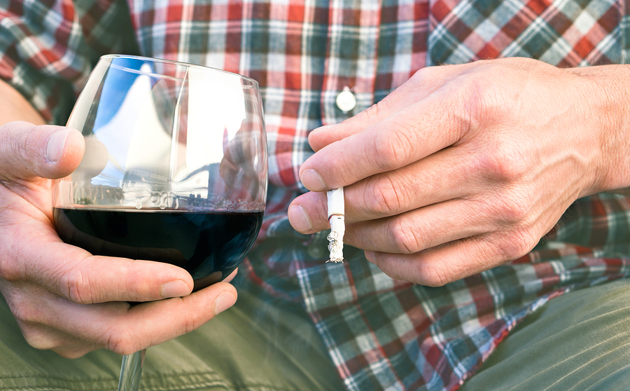 Person drinking a glass of red wine and smoking a cigarette.