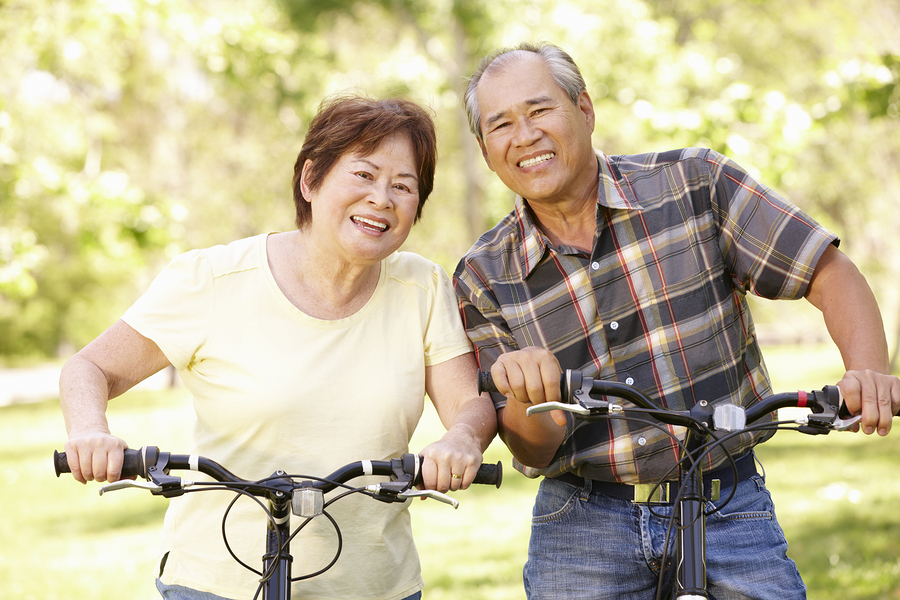 Smiling couple on bicycles.