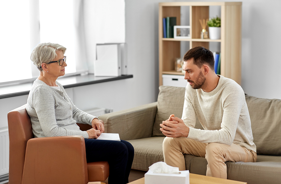 Man sitting on a couch with a therapist across from him.