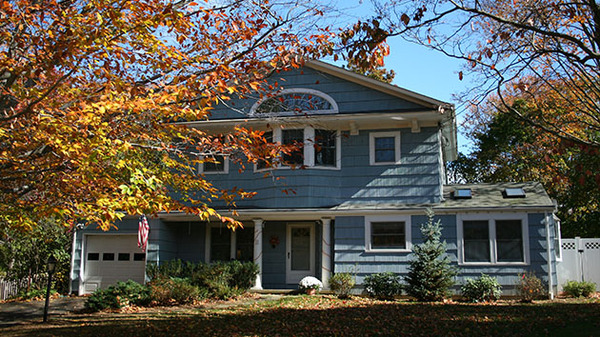 Blue house with white trim and white gutters.