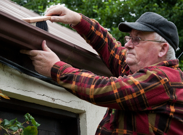 Older man cleaning out his gutters with a brush.